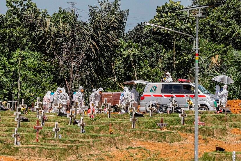 Traslado del feretro con los restos mortales de una víctima de COVID-19 para su entierro en el cementerio de Medan, Indonesia.