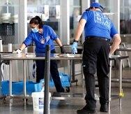 Empleados desinfectan las instalaciones del checkpoint en el terminal 5 del aeropuerto JFK. (AP)