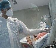 Un médico atiende a un paciente recluido en una Unidad de Cuidados Intensivos por complicaciones de COVID-19.