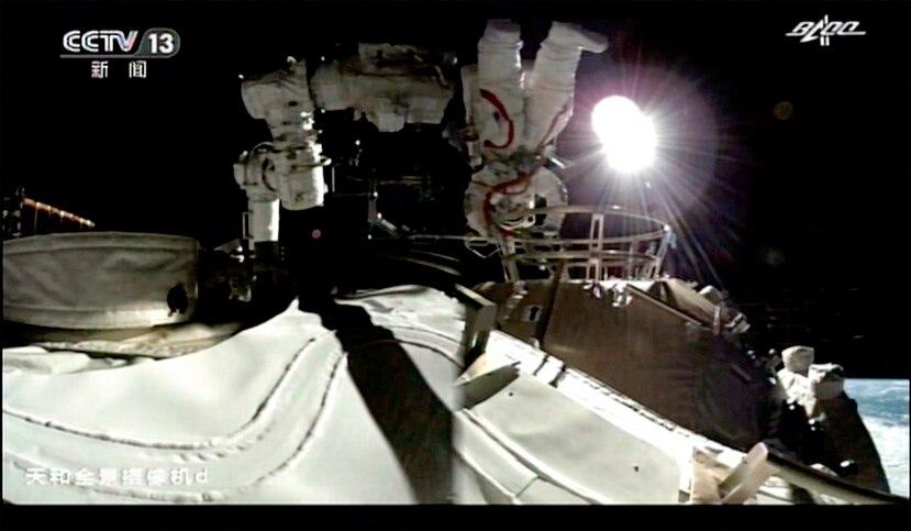 En esta imagen tomada de un video difundido por la televisora estatal china CCTV, Liu Boming sale del módulo principal de la nueva estación espacial china, el domingo 4 de julio de 2021. Dos astronautas hicieron la primera caminata espacial fuera de la nueva estación espacial china, para trabajar en la instalación de un brazo robótico de 15 metros de largo.
