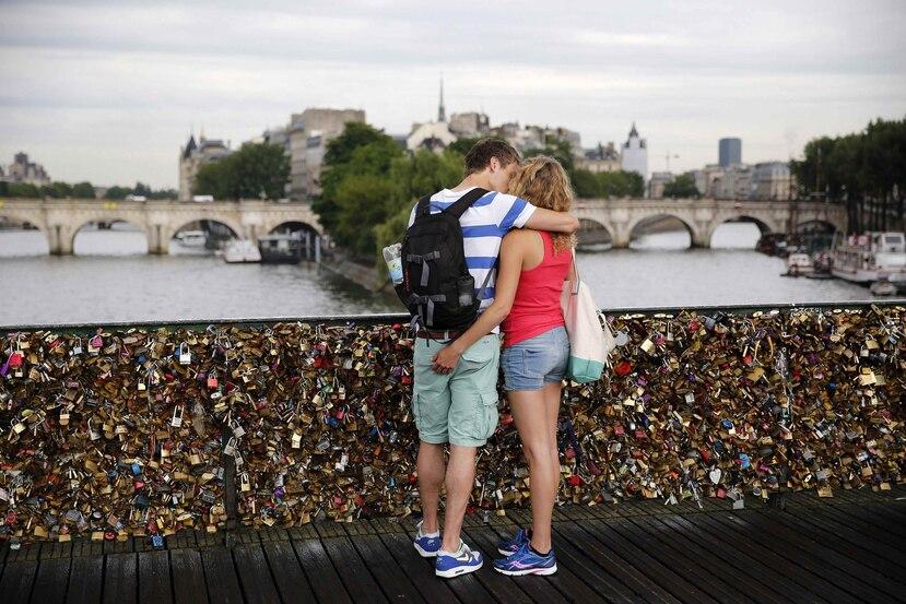 Una pareja se besa en el puente Pont des Arts, en París, Francia. (EFE/Yoan Valat)