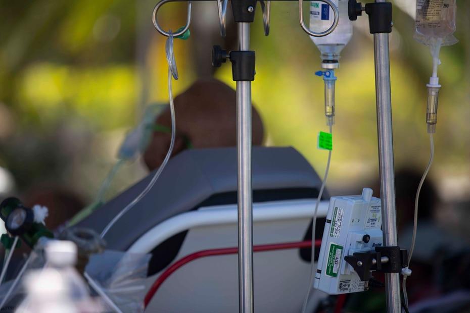 Un paciente encamado aguarda debajo de una carpa para resguardarse del sol.
