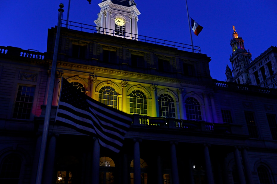 Una bandera de Estados Unidos ondea a media asta frente a la alcaldía de Nueva York, que es alumbrada con los colores de la bandera LGBTT. (AP)