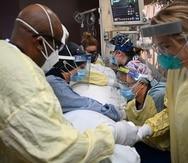 ARCHIVO - En esta foto del 7 de diciembre del 2020, enfermeros de cuidados intensivos y terapeutas respiratorios tratan a un paciente con COVID-19 en el Hospital North Memorial Health en Robbinsdale, Minnesota. (Aaron Lavinsky/Star Tribune via AP)