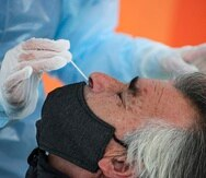 A healthcare worker takes a nasal swab sample from a merchant at a new coronavirus testing site geared at street vendors, at a sports center in the Puente Alto neighborhood of Santiago, Chile, Friday, July 10, 2020. (AP Photo/Esteban Felix)