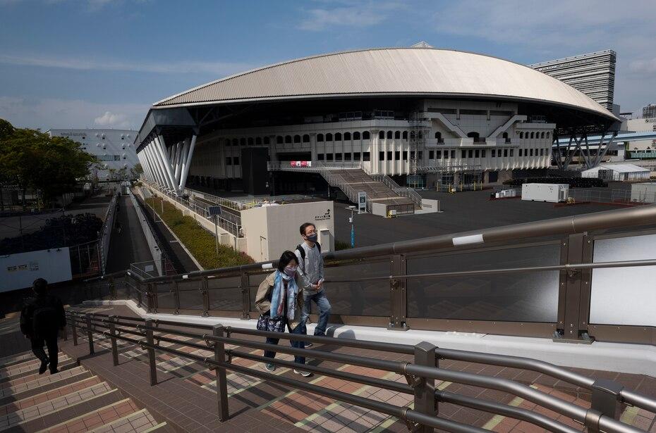 Una pareja camina frente al Coliseo Ariake, una de las sedes de los pospuestos Juegos Olímpicos de Tokio, el jueves 8 de abril de 2021. (AP Foto/Hiro Komae)