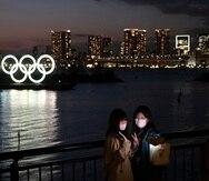 Dos mujeres se toman una selfie frente a los aros olímpicos en la sección de Odaiba en Tokio, el jueves 12 de marzo de 2020. Los juegos se pospusieron debido a la pandemia del nuevo coronavirus. (AP Foto/Jae C. Hong)