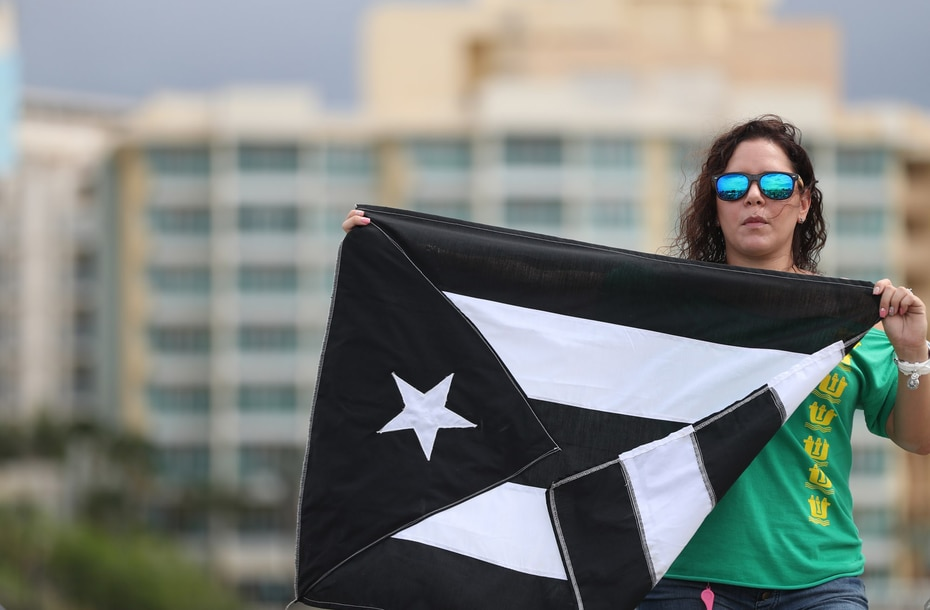 Una manifestante extiende la bandera de Puerto Rico pintada de negro.