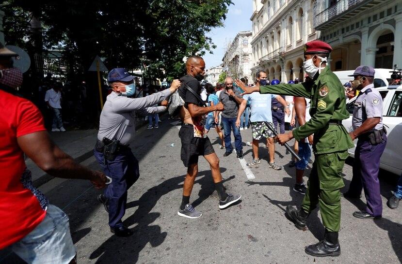 Policías arrestan a un hombre cuando personas se manifiestan hoy, en una calle en La Habana.