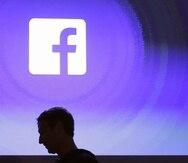 La sombra del fundador de Facebook, Mark Zuckerberg, se observa sobre una pantalla en la que se ve el logo de la empresa. (AP)