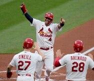 Yadier Molina (4), de los Cardinals de San Luis, celebra con sus compañeros Tyler O'Neill (27) y Nolan Arenado (28) tras anotar con un doble de tres carreras de Matt Carpenter en el primer inning del juego ante los Indians de Cleveland.