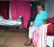 Doña María Ambert cuida de su hijo Juan Manuel -diagnosticado con epilepsia- en una pequeña estructura de madera.