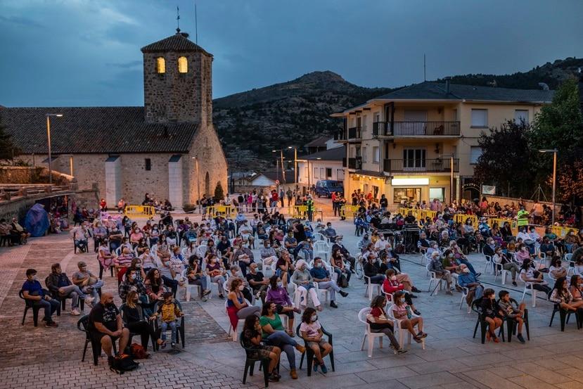 Personas con mascarilla y manteniendo distancia social disfrutan de un espectáculo en las afueras de Madrid, España.