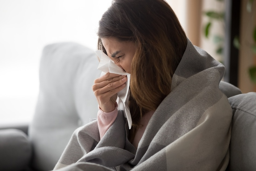 Una mujer estornuda.