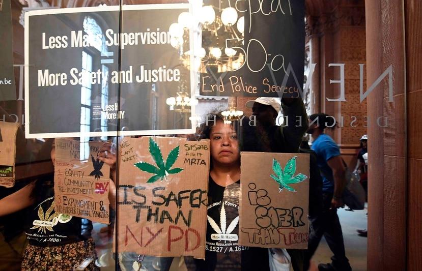 Pilar De Jesús, junto con una coalición de manifestantes, sostiene un letrero exhortando a los legisladores a aprobar la posesión de marihuana contra las puertas del Senado en el Capitolio estatal. (AP)