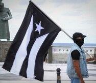 """Un manifestante carga la bandera de """"luto"""" de Puerto Rico."""