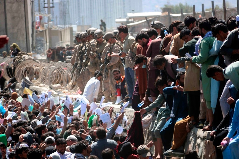 Numerosos afganos muestran credenciales mientras intentan contactar con las fuerzas internacionales para intentar huir del país en los exteriores del aeropuerto Hamid Karzai de Kabul.