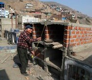 El comerciante retirado Víctor Coba toma medidas de las tumbas que está construyendo para su familia en el cementerio de San Lázaro en las afueras de Lima, Perú.