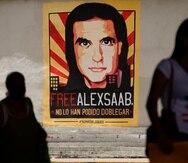 Personas camina cerca de un cartel que pide la liberación del empresario colombiano y enviado especial del gobierno venezolano, Alex Saab, en Caracas, Venezuela.