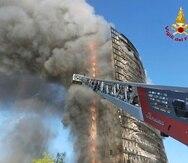 Bomberos intentan controlar el fuego en el condominio en Milán, Italia.