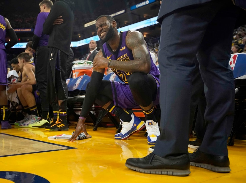 LeBron James luce adolorido en el banco de los Lakers. (AP)