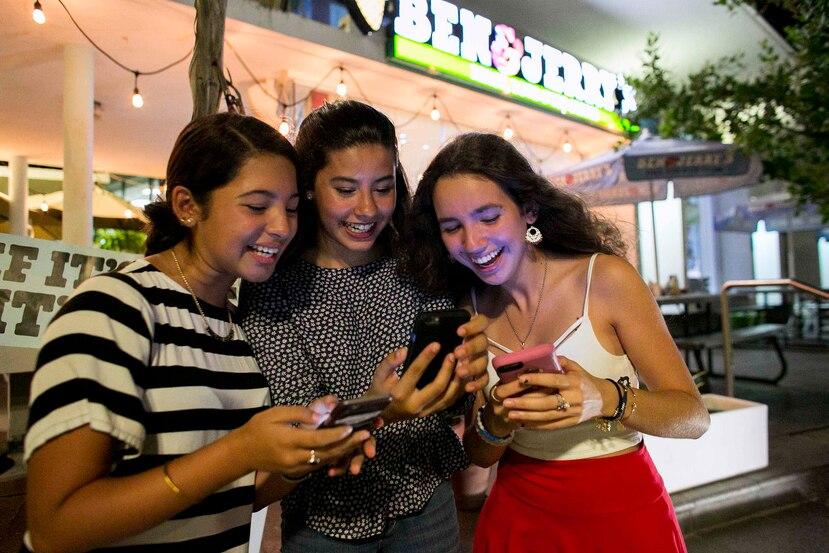 Desde la izquierda, María Rodríguez, Alondra Belaval y Alexandra Piovanetti juegan Pokémon Go frente a una heladería en Condado.