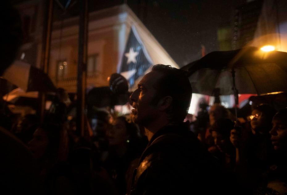 Un manifestante participa en la marcha mientras en el fondo se aprecia una bandera de Puerto Rico.