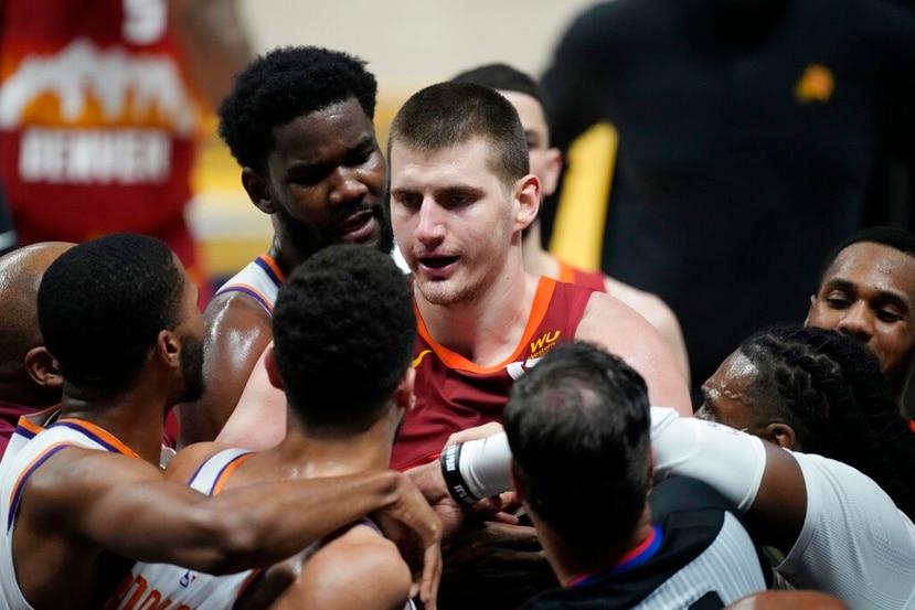 El jugador de los Nuggets de Denver, Nikola Jokic, discute con el escolta de los Suns de Phoenix, Devin Booker, durante la segunda mitad del cuarto juego en la segunda ronda de los playoffs de la NBA.