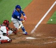 Yadier Molina, de los Cardinals, observa el lanzamiento mientras su compatriota, Javier Báez, dispara un batazo durante el encuentro del domingo.