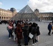 Turistas esperan y empleados en huelga se manifiestan en la entrada al Museo del Louvre. (AP/Francois Mori)