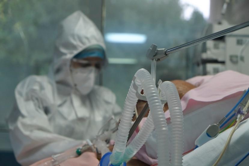 Una enfermera atiende a un paciente recluido en una Unidad de Cuidados Intensivos por COVID-19.