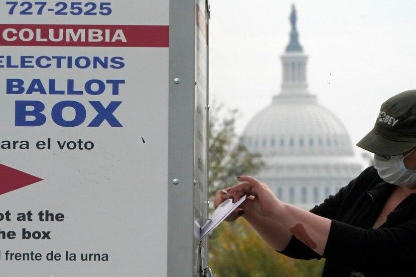 Contra el fondo de la cúpula del Capitolio, un votante coloca su sufragio en una urna de votación anticipada, 28 de octubre de 2020 en el Union Market, Washington.