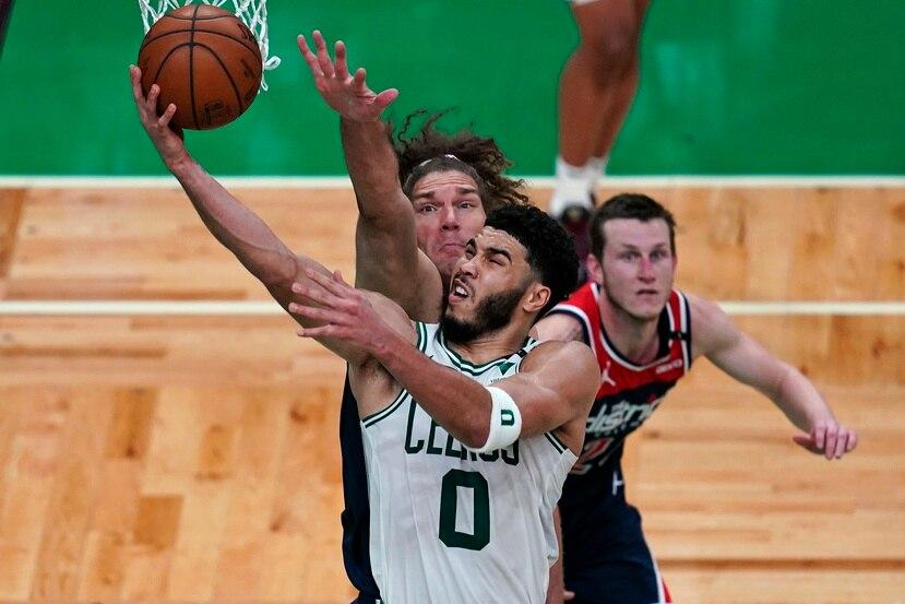 """Jayson Tatum (0) anota contra el centro de los Wizards Robin López en el partido """"play-in"""" de la NBA."""