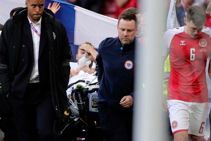 Paramédicos retiran en camilla al jugador danés Christian Eriksen, quien se desvaneció en un partido de la Eurocopa.