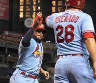 El jugador de los Cardinals de San Luis, Yadier Molina, celebra con Nolan Arenado (28) después de que ambos anotaran en el juego de su equipo contra los Diamondbacks de Arizona.