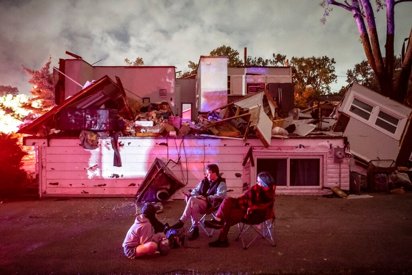 Bridget Casey sits in the driveway of her severely damaged home with her son Nate, 16, and daughter Marion, 14, after a tornado swept through the area in Woodridge, Ill., early Monday morning, June 21, 2021. Officials say a radar-confirmed tornado swept through suburban Chicago late Sunday, damaging homes, toppling trees, knocking out power and causing some injuries.