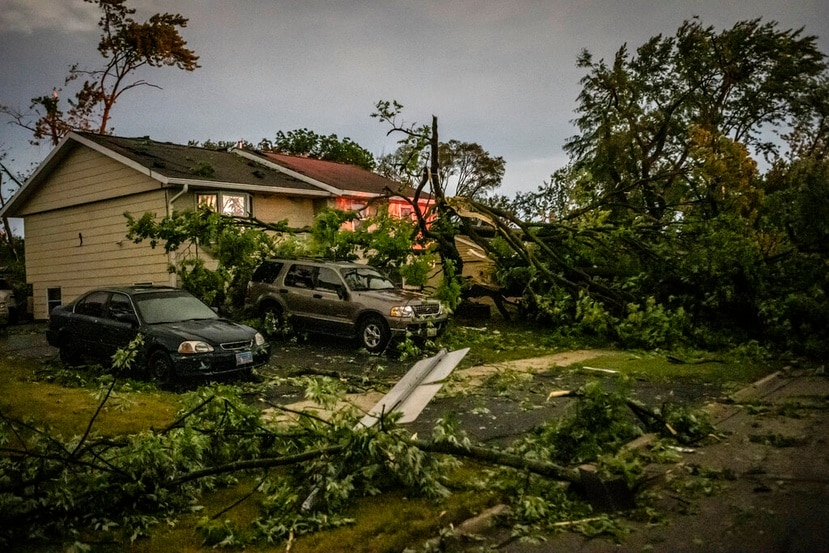 Fallen trees lay in front of a home after a tornado swept through the area in Woodridge, Ill., early Monday morning, June 21, 2021. Officials say a radar-confirmed tornado swept through suburban Chicago late Sunday, damaging homes, toppling trees, knocking out power and causing some injuries.
