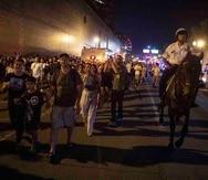 Un grupo de personas sale del muelle Navy, en Chicago, escoltados por la Policía tras las festividades del Día de la Independencia. (AP)