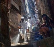 Voluntarios rocían desinfectante en un callejón para ayudar a contener el brote de coronavirus, en la favela de Santa Marta, en Río de Janeiro, Brasil, el 28 de noviembre de 2020. Los voluntarios que han estado higienizando los estrechos callejones y casas de los barrios más pobres de Río realizaron esta tarea por última vez el sábado. El grupo liderado por Thiago Firmino dijo que se ha quedado sin fondos en un momento en que el número de casos de COVID-19 vuelve a repuntar en la ciudad. (AP Foto/Bruna Prado)