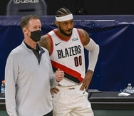 Carmelo Anthony habla con el dirigente Terry Stotts durante el partido de Portland contra Minnesota.