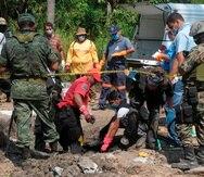 Peritos forenses trabajan en una fosa clandestina de la cual ocho cadáveres fueron rescatados en México.