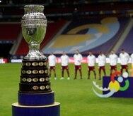 La foto muestra el trofeo de la Copa América delante de los jugadores de Venezuela durante la interpretación de los himnos nacionales, previo al partido inaugural entre ese equipo y Brasil.