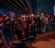 Activistas prodemocracia crean una cadena humana ante las barricadas policiales durante su marcha hacia la Casa de Gobierno, la oficina del primer ministro, durante una protesta en Bangkok, Tailandia, el miércoles 21 de octubre de 2020.
