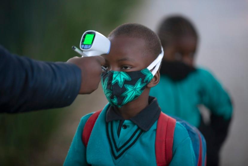 Un adulto comprueba la temperatura corporal de un alumno al regresar a la escuela en Johannesburgo.