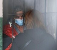 Standing behind bars, Bolivia's former interim President Jeanine Anez speaks to an unidentified woman at a police station jailhouse, in La Paz, Bolivia, Saturday, March 13, 2021. The conservative interim president who led Bolivia for a year was arrested Saturday as officials of the restored leftist government pursue those involved in the 2019 ouster of socialist leader Evo Morales, which they regard as a coup, and the administration that followed. (AP Photo/Juan Karita)