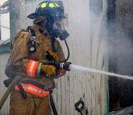 Foto de archivo de un bombero mientras realizaba labores de extinción de incendios en residencias.