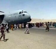 Cientos de personas corren junto a un avión C-17 de las fuerzas armadas de Estados Unidos en el aeropuerto de Kabul en Afganistán. (UGC vía AP)