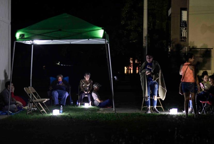 Los vecinos permanecen al aire libre usando tiendas de campaña y luces portátiles por temor a posibles réplicas en su primera noche después de un terremoto de magnitud 6,4 en Guánica, Puerto Rico, el martes 7 de enero de 2020. (Foto AP / Carlos Giusti)