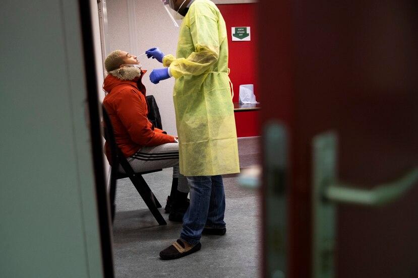 Un trabajador de la Cruz Roja toma una muestra para una prueba molecular de COVID-19.