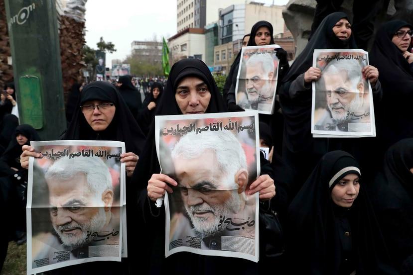 Personas sujetan fotos de Qassem Soleimani. (AP)